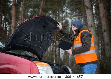man driver wearing a high visibility vest  bending over the engine of his broken down car during winter time #1306141657
