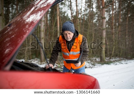 man driver wearing a high visibility vest  bending over the engine of his broken down car during winter time #1306141660