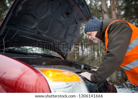 man driver wearing a high visibility vest  bending over the engine of his broken down car during winter time #1306141666