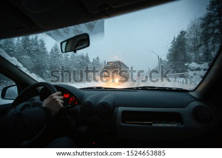 Man drives a car during winter speedway in a snow storm in the twilight when snow with rain is flying. Concept of driving in the dangerous conditions with bad visibility on the winter. #1524653885