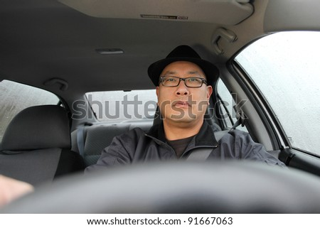 Man driving a car on a rainy day. - stock photo