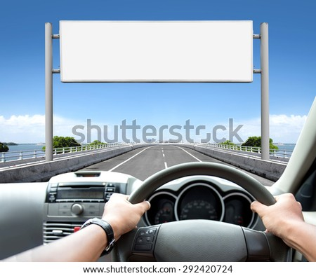 Man driving a car while looking at billboard or road sign ahead #292420724