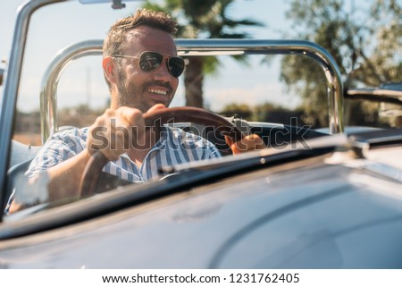 Man driving a convertible vintage car #1231762405