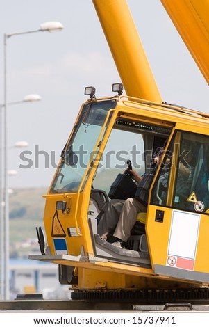 Man driving a crane to lift-up some equipments