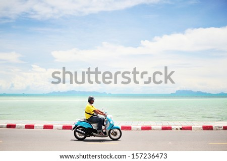 Man driving a motorcycle along the road, blue sea-sky background.