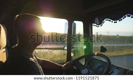 Man driving a truck and carefully watching the road. Caucasian guy is riding through the countryside on the sunset background. Profile of lorry driver inside the cab. Side view Slow motion Close up