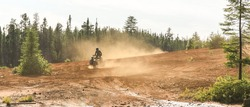 Man driving ATV quad in sandy terrain with high speed.