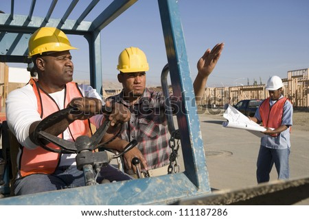 Man driving bulldozer at construction site among other workers