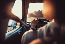 Man driving car, hand on steering wheel, looking at the road ahead,sunset.