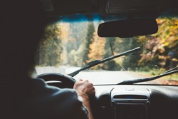 Man driving car in rain weather. Fall trip. Wipers cleaning windshield. Freedom travel concept. Autumn weekend.
