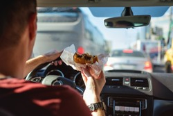 Man driving car while eating hamburger. Waiting and standing in traffic jam