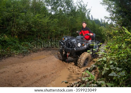 Man driving four-wheeler ATV through mud #359923049