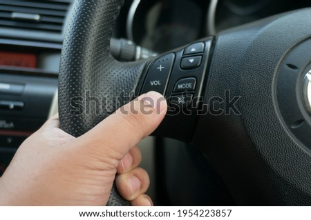 Man driving hands pushing button on the steering wheel in the car selective focus. safety driving car Foto d'archivio ©