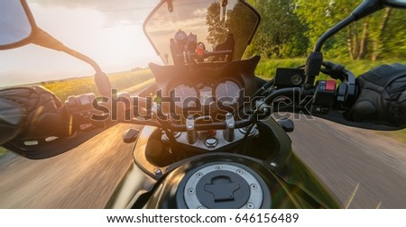 Man driving his motorcycle on asphalt country road. Summer sunset #646156489