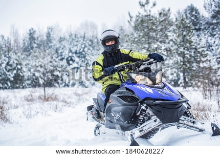 Man driving snowmobile in snowy forest. Man on snowmobile in winter mountain. Snowmobile driving. Stock photo ©