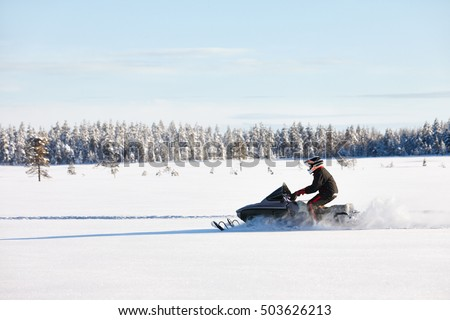 Man driving sports snowmobile in Finnish Lapland in a sunny day Stock photo ©