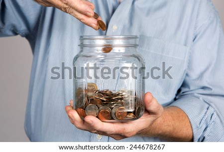 Man drops money into a glass jar for a savings account. Foto stock ©