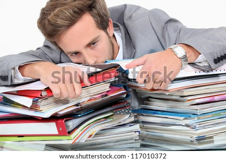 Man drowning in stacks of paperwork