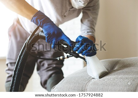 Man dry cleaner's employee hand in protective rubber glove cleaning sofa with professionally extraction method. Early spring regular cleanup. Commercial cleaning company concept. Closeup