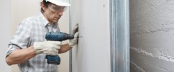 man drywall worker or plasterer using cordless electric screwdriver to fix the plasterboard sheets to the metal profiles to build the new wall . Wearing white hardhat, work gloves and safety glasses