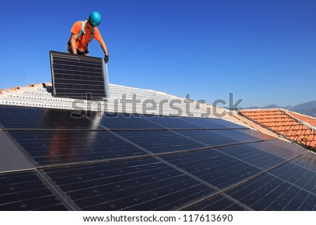 Man during intallation of alternative energy photovoltaic solar panels on roof
