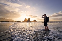 Man during photographing landscape with cliff. Young photographer on beach at beautiful sunset. Tenerife, Canary Islands, Spain.