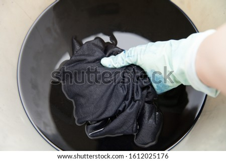 man dyeing clothes in bucket Stockfoto ©