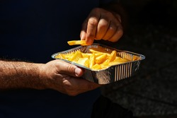 Man eat yummy french fries in aluminium foil tray. Fast food o street food takeaway service concept.