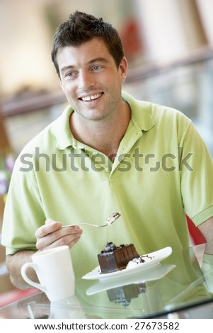 Man Eating A Piece Of Cake At The Mall
