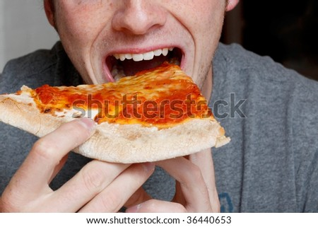 Man eating a pizza slice - stock photo