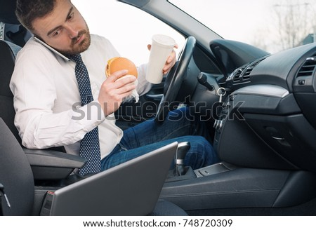 Man eating an hamburger and working seated in his car #748720309