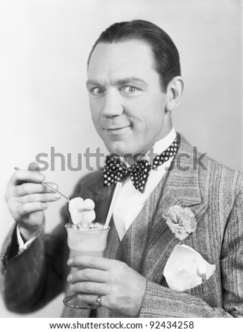 Man eating an ice-cream out of a glass with a straw