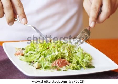 Man, eating Caesar salad with salmon