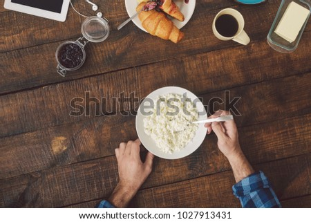 Man eating cottage cheese, top view. Healthy breakfast concept