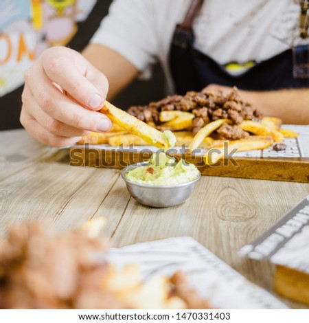 Man eating french fries with beans