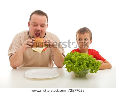 Man eating hamburger and boy with salad watching - healthy eating teaching by example concept
