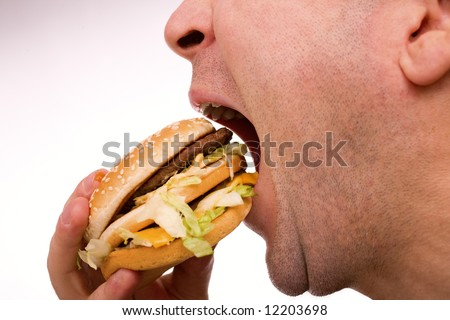 Man eating hamburger over white - stock photo