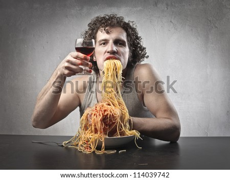 Man eating pasta and drinking red wine - stock photo