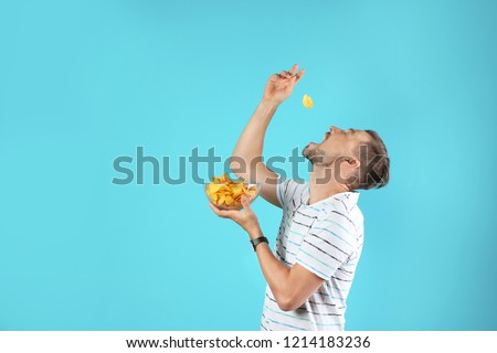 Man eating potato chips on color background. Space for text