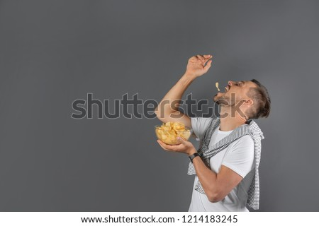 Man eating potato chips on grey background. Space for text