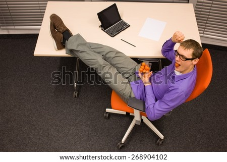 man eating raw food - tomatoes - in his office