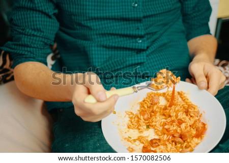 Man eats. Human eats pasta on a Sunny day.