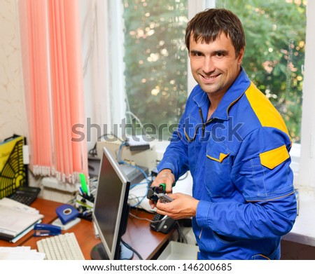 man electrician installs electrical network in the office