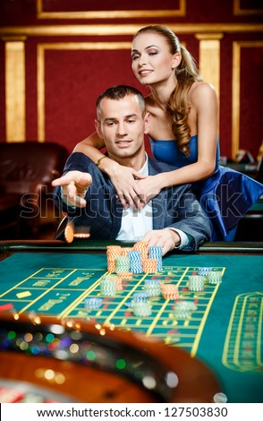 Man embraced by pretty girl throws the chip on the casino table