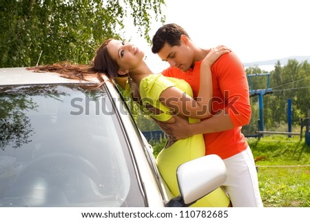 man embraces a young girl at the car
