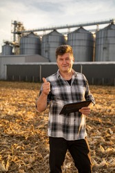 Man engineer  with tablet showing thumbs up outside the agricultural silo