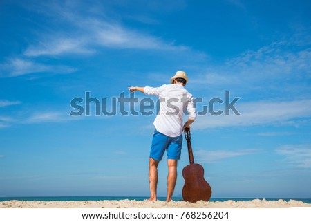 man enjoy life with the nature at the sea beach by hold guitar in hand, daylight sunny enjoyment in holiday long weekend #768256204