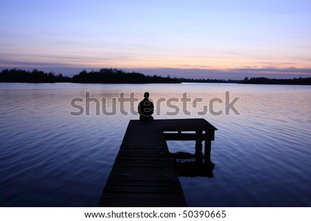 Man enjoying a spring sunset from a small pier at a lake. - stock photo