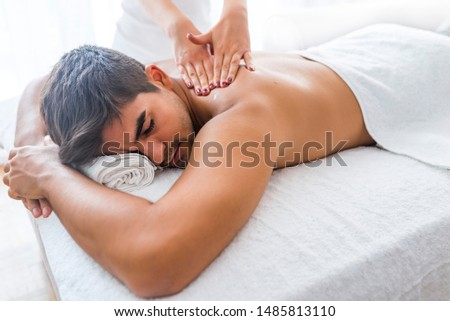 Man Enjoying Massage At Spa. Man having back massage at the health spa. Sports massage. Close-up of masseur's hands and a client's back. Man has deep tissue massage on the back.