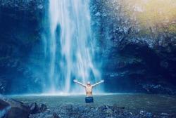 Man enjoying pool at the base of large waterfall in Hawaii